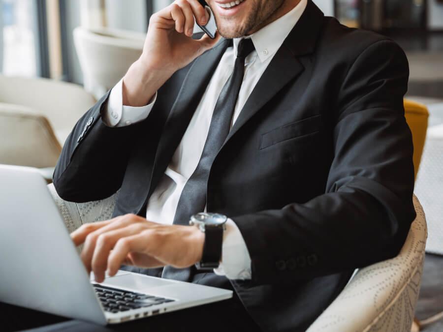 パソコンを触りながら電話をする男性